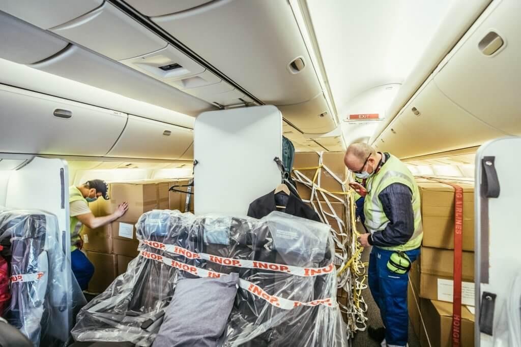 Erste Kartons mit medizinischer Ausrüstung werden in die Kabine gebracht und verstaut. © DB Schenker