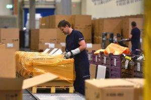 Ein Mitarbeiter von DB Schenker verpackt BMW-Komponenten. © Ralf Lehmann/Schenker Deutschland AG