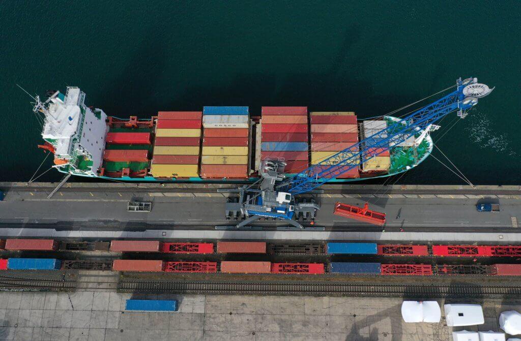 Seehafen Rostock: Ein Kran lädt Container mit Schutzausrüstung für Italien vom Schiff auf bereit stehende Güterwaggons. © DB Schenker