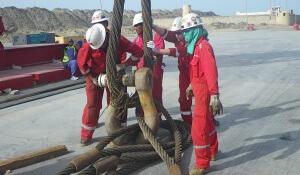 Arbeiter in roten Overals und mit Schutzhelmen an dicken Tauen
