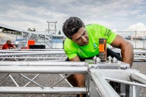 Mitarbeiter prüft Grid mit Laser-Messgerät